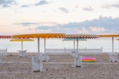 De zomerzeegezicht met witte ligstoelen onder kleurrijke strandparaplu's stock foto's