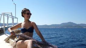 De de zomerzeereis, de rijke gelukkige vrouw in oogglazen en het badpak ontspannen op boog van jacht en doek het golven stock video