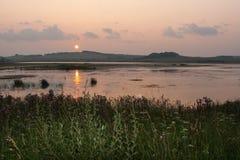 De zomerzonsondergang over vijver en klein dorp achter hem Royalty-vrije Stock Afbeeldingen
