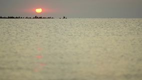 De zomerzonsopgang boven zwarte rotsen door de overzeese kusten stock videobeelden
