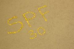 De zon beschermt factorenspf 30 woord op het zand met gele stenen wordt geschreven die Het conceptenachtergrond van de huidzorg stock afbeeldingen
