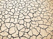 De zon bleekte droge gebarsten aarde Stock Foto