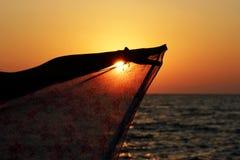 De zon daalt in het overzees bij zonsondergang en glanst door de sjaal van pareo, die door de hand van jongelui wordt gehouden royalty-vrije stock foto's