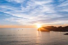 De zon die achter Dubrovnik met een levendige hemel plaatsen Stock Fotografie