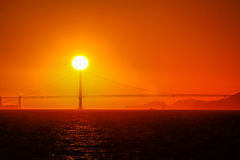 De zon die achter Golden gate bridge in San Francisco Bay plaatsen Stock Afbeeldingen