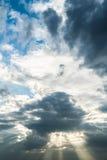 De zon die door donkere onweerswolken met hemelachtergrond breken Stock Foto