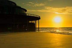 De zon die die in het overzees dalen algemeen als zonsondergang wordt bekend stock foto's