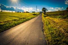 De zon die over een landweg dichtbij Dwarswegen plaatsen, Pennsylvan royalty-vrije stock foto's