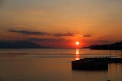 De zon die over het overzees optekenen, de rode schijf van de zon raakt de horizon Royalty-vrije Stock Afbeelding