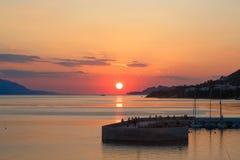 De zon die over het overzees optekenen, de rode schijf van de zon raakt de horizon Stock Foto