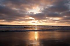 De zon die in de Vreedzame die oceaan plaatsen van een strand wordt gezien stock afbeeldingen