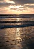 De zon die in de Vreedzame die oceaan plaatsen van een strand wordt gezien royalty-vrije stock afbeelding