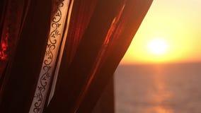 De zon glanst door een gordijn tijdens zonsondergang met overzeese mening en de mooie gevolgen van de lensgloed Langzame Motie 19 stock video