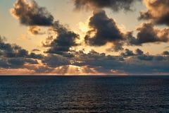 De zon heft uit op op zee stock afbeelding