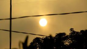 De zon kijkt volkomen rond en geel, omdat de voorwaarde van de hemel donker is stock foto's