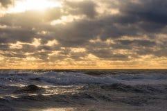 De zon maakt zijn manier door de wolken aan het overzees Royalty-vrije Stock Foto