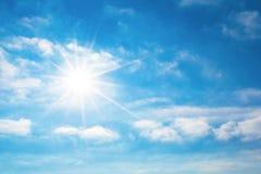 De zon met heldere stralen in de blauwe hemel met witte lichte wolken Stock Foto's