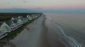 De zon neemt op de eerste Huizen van het rij oceanfront strand, het Eilandpijler van het Noordentopsail, het Strand van het Noord stock videobeelden
