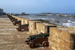 De zon neemt overarij van canons bij de vroegere vesting toe in Essaouira in Marokko Stock Afbeeldingen