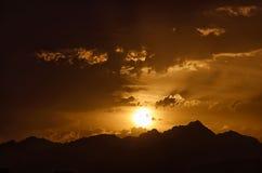 De zon ontmoet de horizon achter bergen Royalty-vrije Stock Foto's