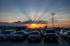 De zon plaatst op schemering dramatische hemel, over auto's, op hoogste r stock afbeelding