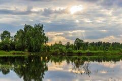 De zon` s stralen die door de wolken breken De Rivier Mologa stock foto