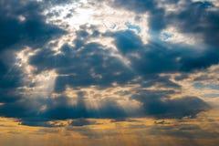 De zon` s stralen die door de wolken, onweerswolken op zee breken stock foto