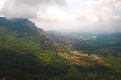 De zon` s stralen die hun manier maken door de wolken de voet van de berg verlichten royalty-vrije stock afbeelding