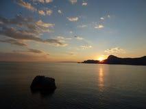 De zon staat achter de bergen te verbergen op het punt Sudak Stock Afbeelding