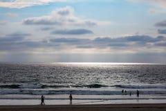 De zon straalt door een wolk uit en leidt tot oceaanschijnwerper stock afbeeldingen