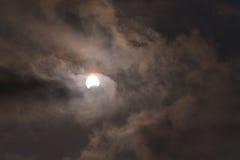 De zon tijdens een gedeeltelijke zonneverduistering met donkere wolken Stock Fotografie