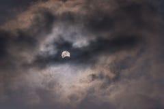 De zon tijdens een gedeeltelijke zonneverduistering met donkere wolken Stock Afbeelding