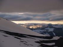 De zon van de middernacht over de sneeuwbergen Stock Foto