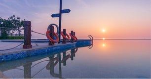De zon, zonsondergang, zonsonderganggloed, kalme meeroppervlakte, verkeersteken, een stil beeld royalty-vrije stock foto's