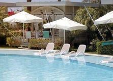 De zonbedden in het zwembad voor ontspannen op mooie de zomerreso royalty-vrije stock foto's
