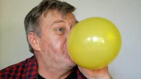 De zonderlinge hogere mens, met grijs haar blaast een ballon op, dan doordrongen en uitbarstingen het en schreeuwen die luid, van stock video