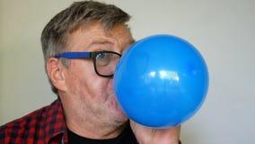 De zonderlinge hogere mens, met grijs haar blaast een ballon op, dan doordrongen en uitbarstingen het en schreeuwen die luid, van stock videobeelden