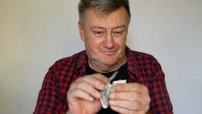 De zonderlinge hogere mens met grijs haar houdt een bankbiljet van honderd Amerikaanse dollars in zijn handen en is gek gelukkig  stock video