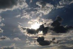 De zonlicht van de silhouethemel op de donkere achtergrond van de wolken blauwe hemel Stock Fotografie
