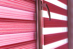 De zonneblinden van de stoffenrol op het venster stock afbeeldingen