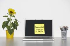 De zonnebloeminstallatie op bureau en het kleverige schrijfpapier met Italiaanse teksten op laptop het scherm die Trascorrere del  Stock Foto's
