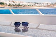 De zonnebril ligt op een lijst aangaande een wit jacht tegen de achtergrond van het overzees en de kust Stock Afbeeldingen