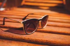 De zonnebril ligt op het hout van de zonlanterfanter Stock Foto's