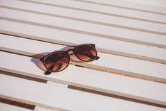 De zonnebril ligt op het hout van de zonlanterfanter Royalty-vrije Stock Foto's
