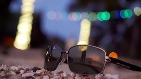De zonnebril ligt op tropisch strand en silhouet van het jonge die spinnen rond paar de achtergrond wordt overdacht Langzame Moti stock videobeelden