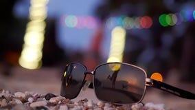 De zonnebril ligt op tropisch strand en silhouet van jong koesterend die paar de achtergrond wordt overdacht Langzame Motie De zo stock video