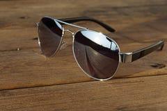 De zonnebril is op de houten lijst Royalty-vrije Stock Afbeeldingen
