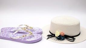 De zonnebril van de hoedenpantoffels van de vrouw en overzeese shell op de witte achtergrond - houd motie tegen stock video
