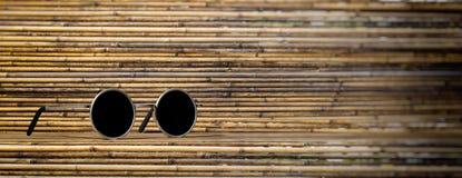 De zonnebril verzilvert om kader met zwarte lens, op een bamboeachtergrond, banner, 3d illustratie Stock Foto
