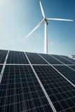 De zonnepanelen en een windmolen produceren elektriciteit van de zon stock afbeelding